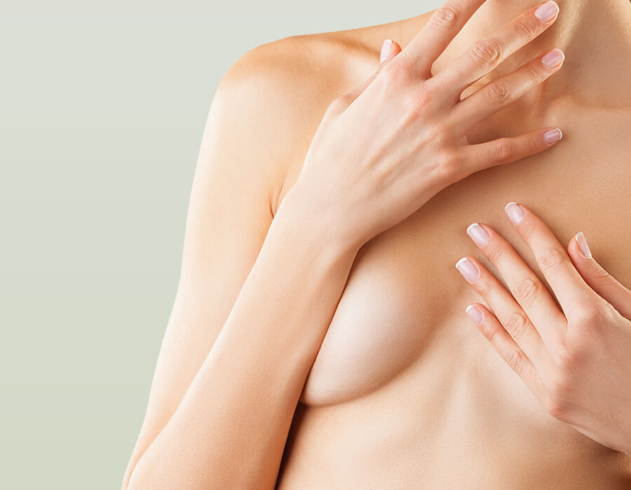Attractive form of woman with hands over breasts.